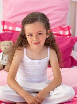 Petite fille assise sur le lit