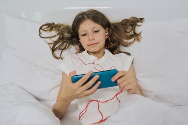 Petite fille assise à la maison dans son lit, avec smartphone et casque