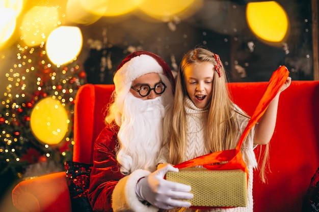 Petite fille assise avec le père noël et des cadeaux à noël