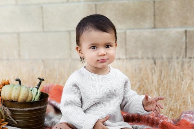 Petite fille assise en plein air avec seau de citrouilles