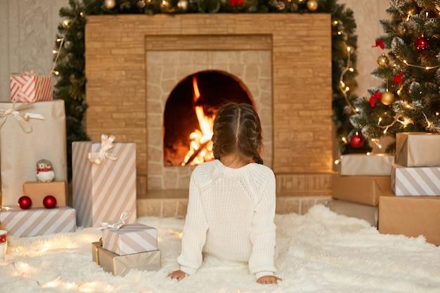 Petite fille assise près d'une cheminée la veille de noël, regardant le feu alors qu'elle était assise sur un tapis moelleux, attendant le réveillon du nouvel an, veut ouvrir ses boîtes à cadeaux.