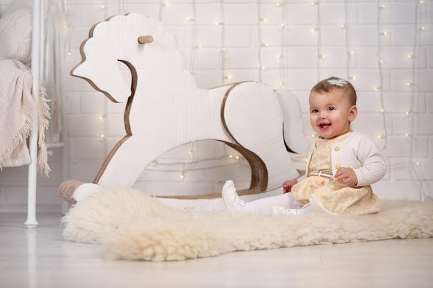 Petite fille assise près d'un cheval à bascule et d'un mur de briques avec une guirlande d'ampoules