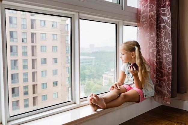Petite fille assise sur le rebord à la maison, regardant par la fenêtre et tenant une pomme rouge