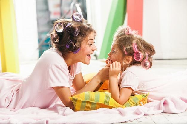 Petite fille assise avec sa mère et jouant