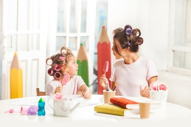Petite fille assise avec sa mère et manger de la glace