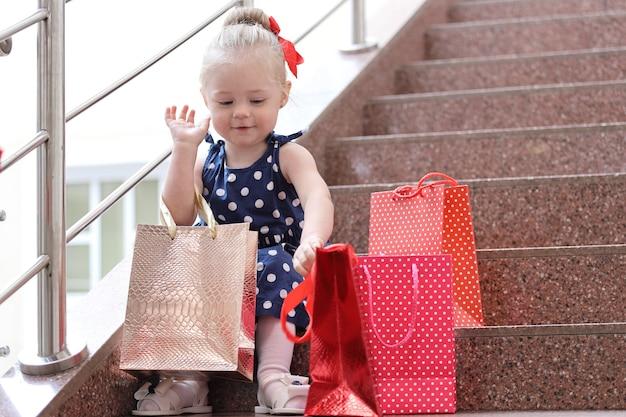Petite fille assise avec des sacs colorés sur les marches du centre commercial.