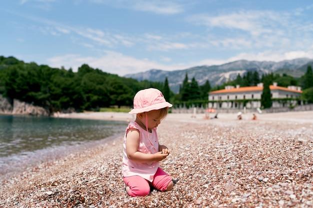 Petite fille assise sur ses genoux sur la plage au bord de l'eau villa milocer