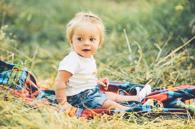 Petite fille assise seule sur la pelouse