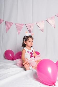 Une petite fille assise sur le sol avec une couronne de corne de licorne faisant des gestes.