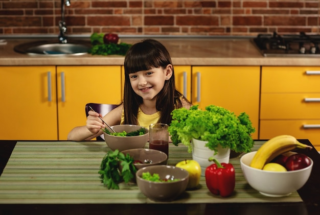 Petite fille assise à une table dans la cuisine et mange une salade.