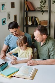 Petite fille assise à la table et étudiant avec ses parents lui apprenant qu'ils étudient à la maison
