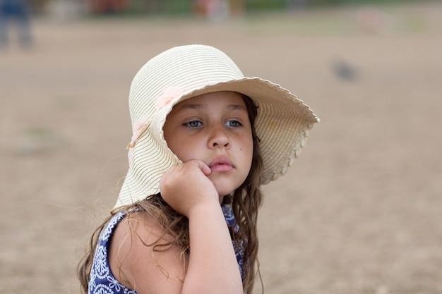 Petite fille assise et tenant un chapeau d'été et une belle robe sur la plage