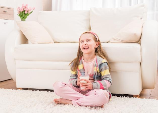 Petite fille assise avec un verre de lait