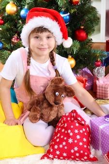 Petite fille au bonnet de noel près de l'arbre de noël dans une salle décorée de façon festive