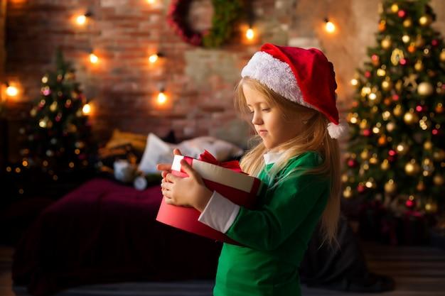 Petite fille au bonnet de noel tenant une boîte-cadeau