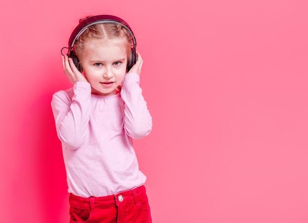 Petite fille au casque sur fond rose