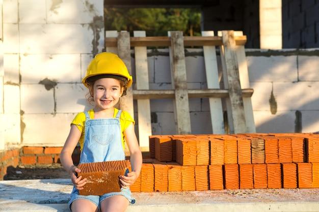 Une petite fille au casque jaune joue au constructeur sur le chantier de sa future maison. attente de déménagement, choix d'une profession, éducation des enfants. futur métier, entreprise familiale.