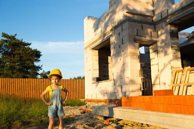 Une petite fille au casque jaune joue au constructeur sur le chantier de sa future maison. rêves de déménagement, choix d'un métier, éducation des enfants.