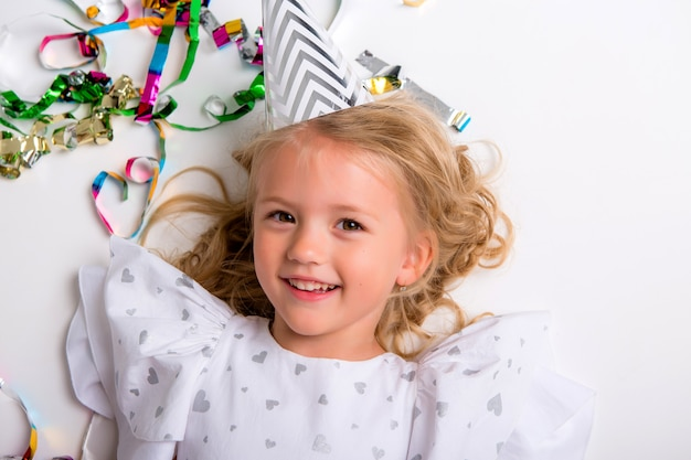 Petite fille au chapeau d'anniversaire souriant avec boîte-cadeau et confettis