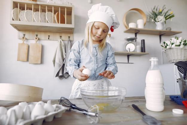 Petite fille au chapeau blanc de shef cuire la pâte pour les biscuits
