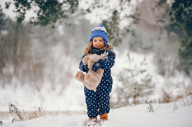 Petite fille au chapeau bleu jouant dans une forêt d'hiver