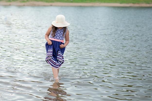 Petite fille au chapeau d'été et belle robe debout dans la rivière