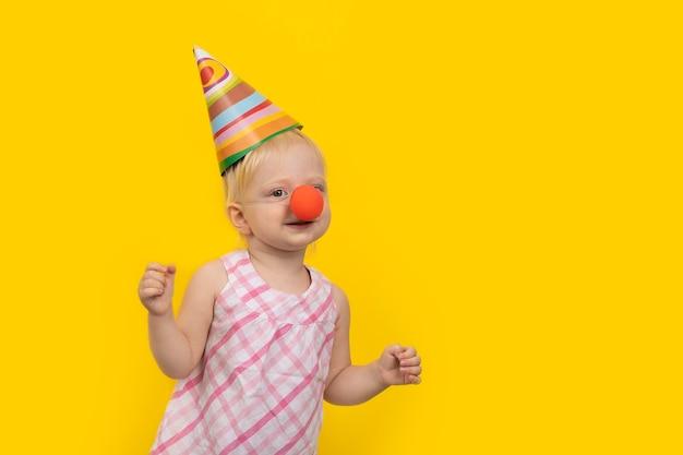 Petite fille au chapeau de fête et nez de clown sur fond jaune.