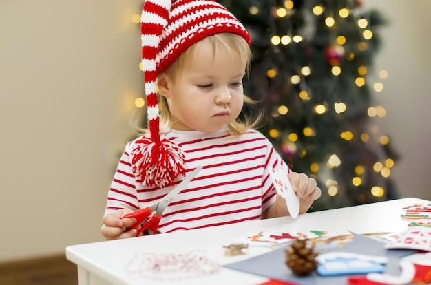 Petite fille au chapeau de noël faisant des décorations pour la créativité des enfants de noël et l'artisanat de noël