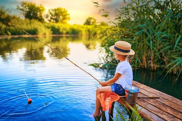 Petite fille au chapeau de paille assis sur le bord d'un quai en bois et pêche dans le lac au coucher du soleil.