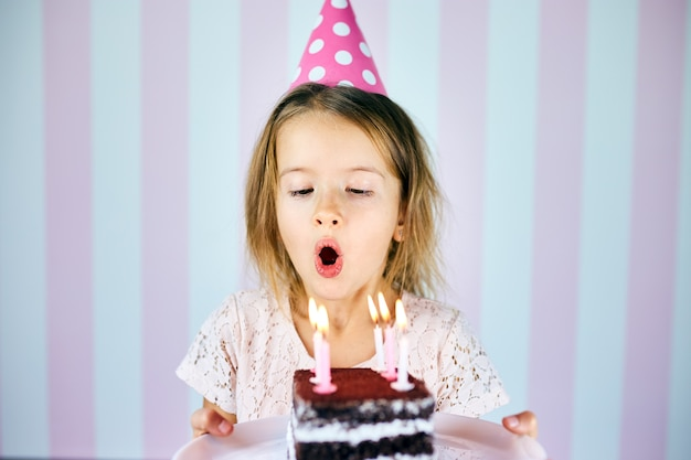 Petite fille au chapeau rose soufflant des bougies sur un gâteau au chocolat d'anniversaire