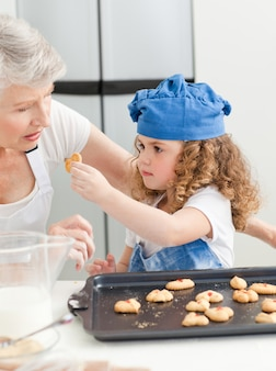 Une petite fille au four avec sa grand-mère