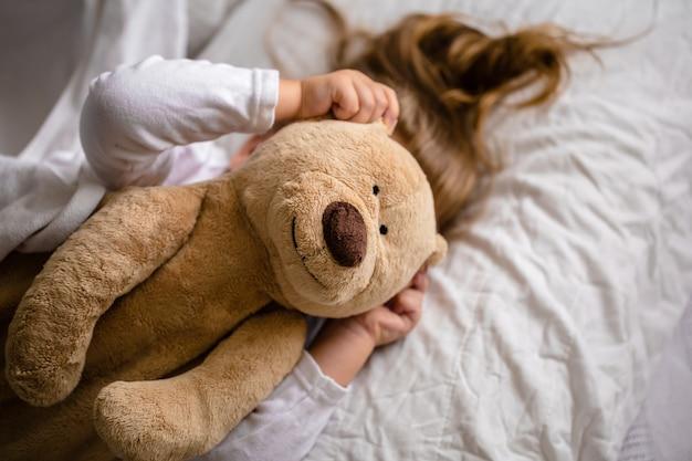 Petite fille au lit avec peluche les émotions d'un enfant