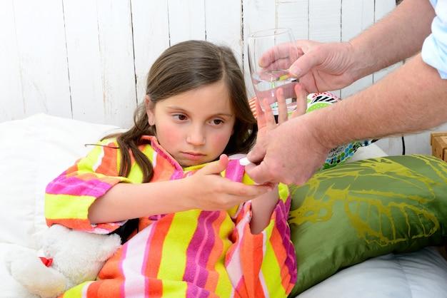 Une petite fille au lit en prenant la tablette