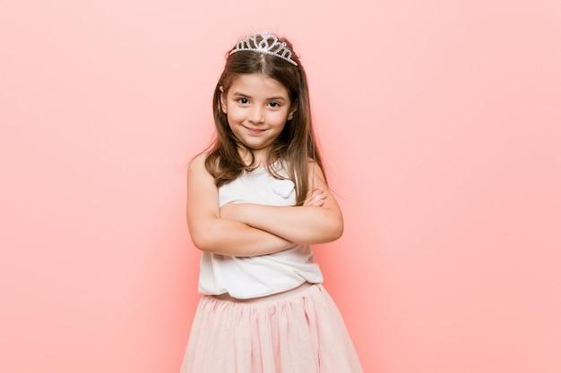 Petite fille au look de princesse qui se sent confiante, croisant les bras avec détermination.