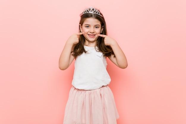 La petite fille au look de princesse sourit et pointe ses doigts vers la bouche.