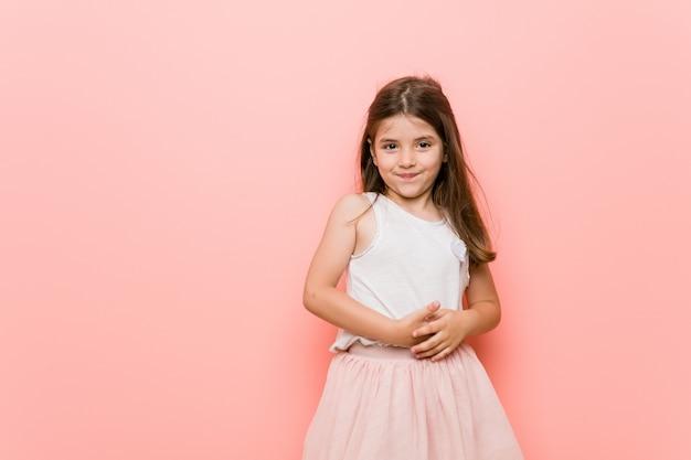 Petite fille au look de princesse touche le ventre et sourit doucement