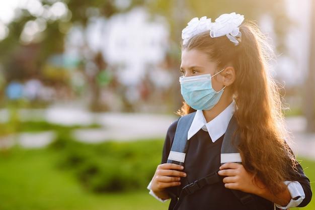 Petite fille au masque médical retour à l'école. écolière portant un masque médical.