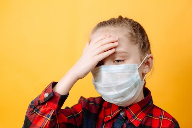 Une petite fille au masque de protection sur un mur jaune. peur d'être infecté
