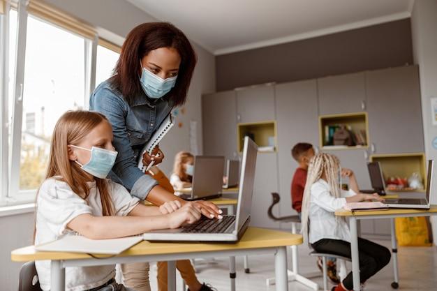 Petite fille au masque utilisant un ordinateur portable et assise au bureau dans la salle de classe