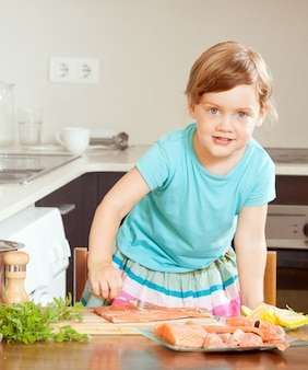 Petite fille au poisson saumon cru