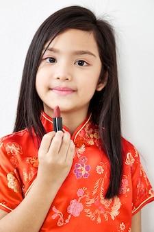 Petite fille au rouge à lèvres