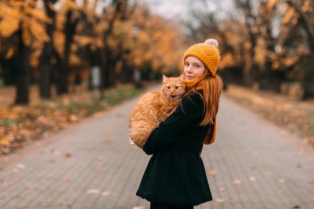 Petite fille au visage de taches de rousseur tenant son chat dans le parc en automne.