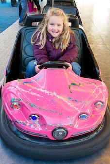 Petite fille au volant d'une voiture tamponneuse