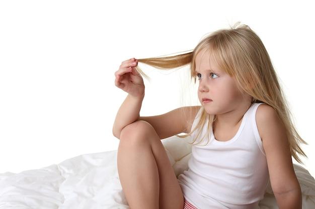 Petite fille aux cheveux blonds au lit