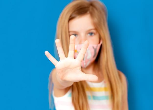 Une petite fille aux cheveux blonds dans un masque médical pour protéger les pm2.5 et montre un geste de la main d'arrêt pour arrêter l'épidémie du virus corona. symptômes du coronavirus et du virus épidémique.