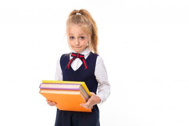 Une petite fille aux cheveux blonds farcis dans une queue de cheval, de grands yeux bleus et un joli visage porte des livres lourds