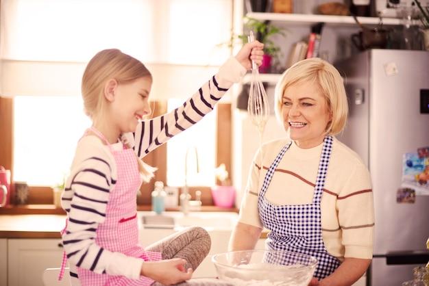 Petite fille aux cheveux blonds mélangeant la farine
