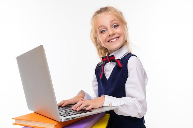 Une petite fille aux cheveux blonds en peluche dans une queue de cheval, de grands yeux bleus et un joli visage avec un ordinateur portable sur les livres.