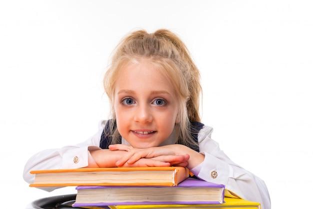Une petite fille aux cheveux blonds en peluche avec une queue de cheval, de grands yeux bleus et un joli visage avec des livres.