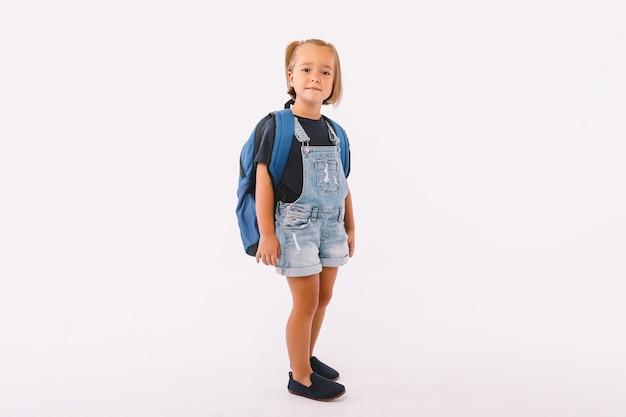 Petite fille aux cheveux blonds vêtue d'une salopette bleue et d'un t-shirt, avec un sac à dos prêt pour la rentrée, sur fond blanc